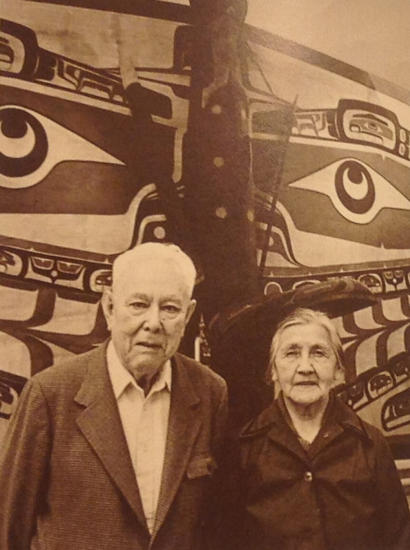 Chief Bill Scow and Alice Scow stand in front of Pacific Science Center's Sea Monster House in 1980. The house was a reconstruction of Scow's home on Gilford Island, and Scow helped provide educational material for the exhibit.
