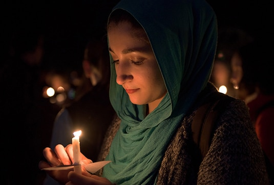 A woman holds a candle at a vigil for victims of the November 13 terrorist attacks in Paris.  Photo: Penn State, via Flickr/Creative Commons